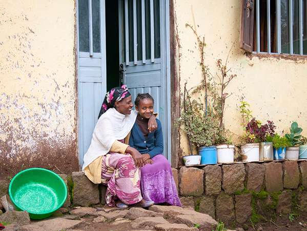ethiopian woman hugs her teenage daughter as they sit on the steps outside their home