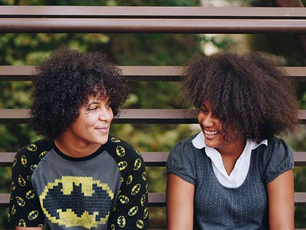 Two teenage siblings with dark curly hair sit outside on bleachers looking at one another smiling.