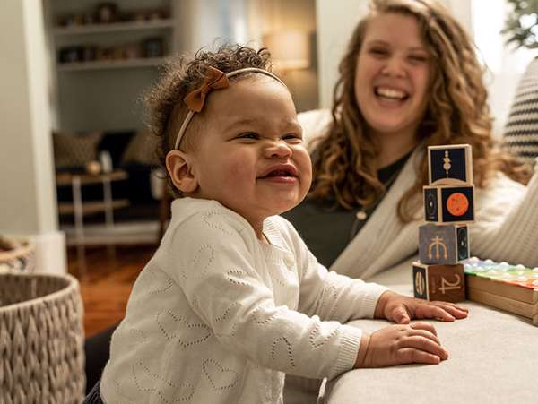 african american toddler smiles while playing with blocks with her adoptive mom