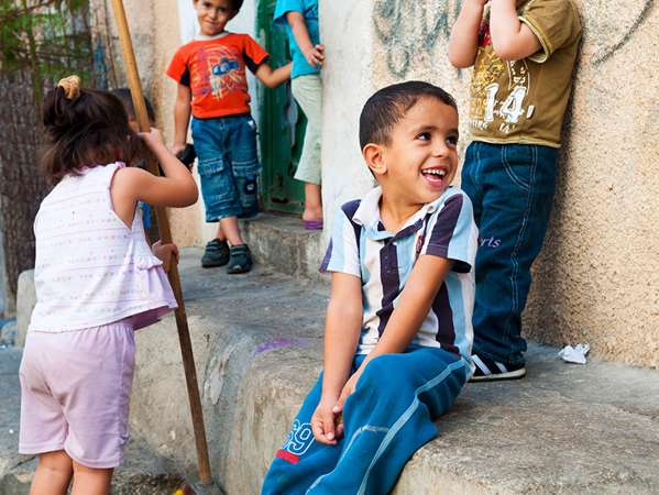 young refugee boy smiles while sitting on a step with his friends