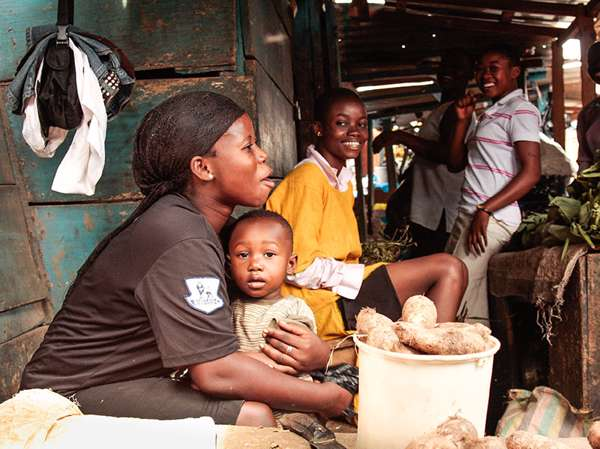 A Ghanaian mother hugs her young son while selling potatoes at the market