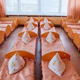 identical, small orange beds fill a room at an orphanage
